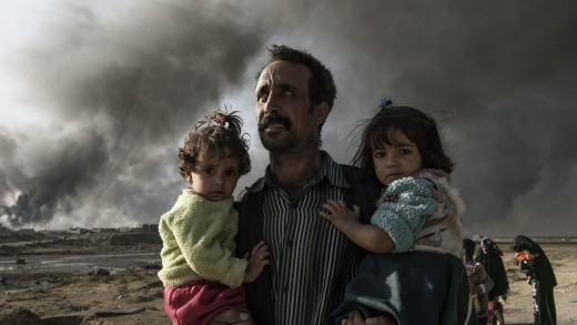 Iraq, Qarayya: A newly displaced man carries two children at the northern check point in Qayyarah, south of Mosul on October 31, 2016. Alessio Romenzi